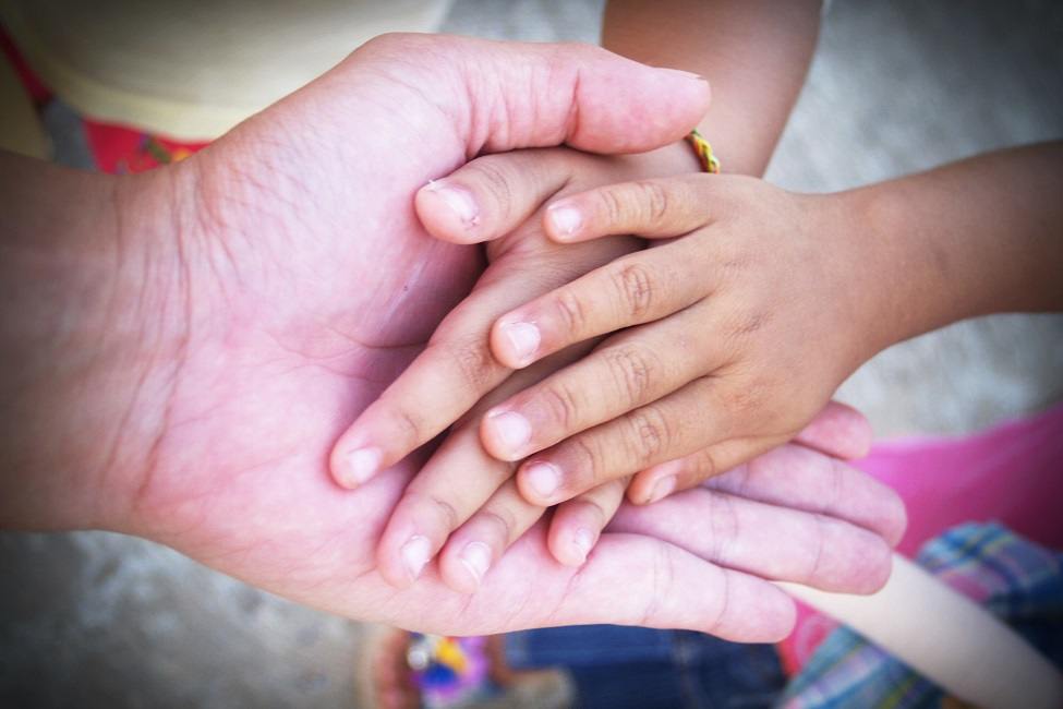 A photo of an adult holding a child's hands