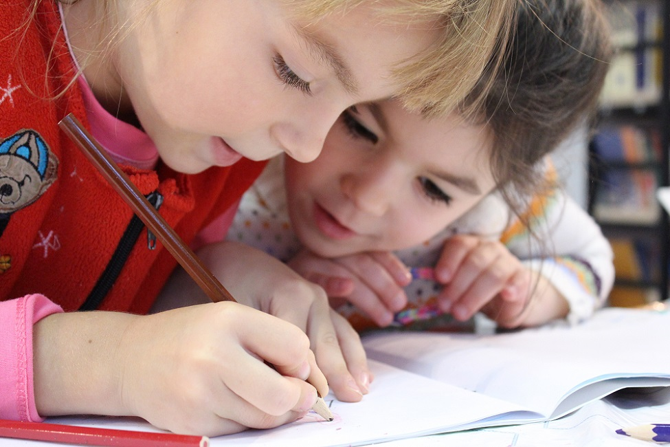 A photo of two children drawing together